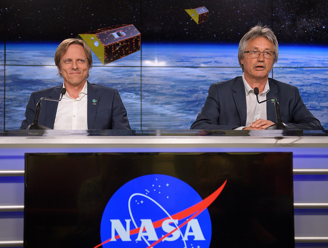 Two scientists sit on a podium with a large NASA logo.
