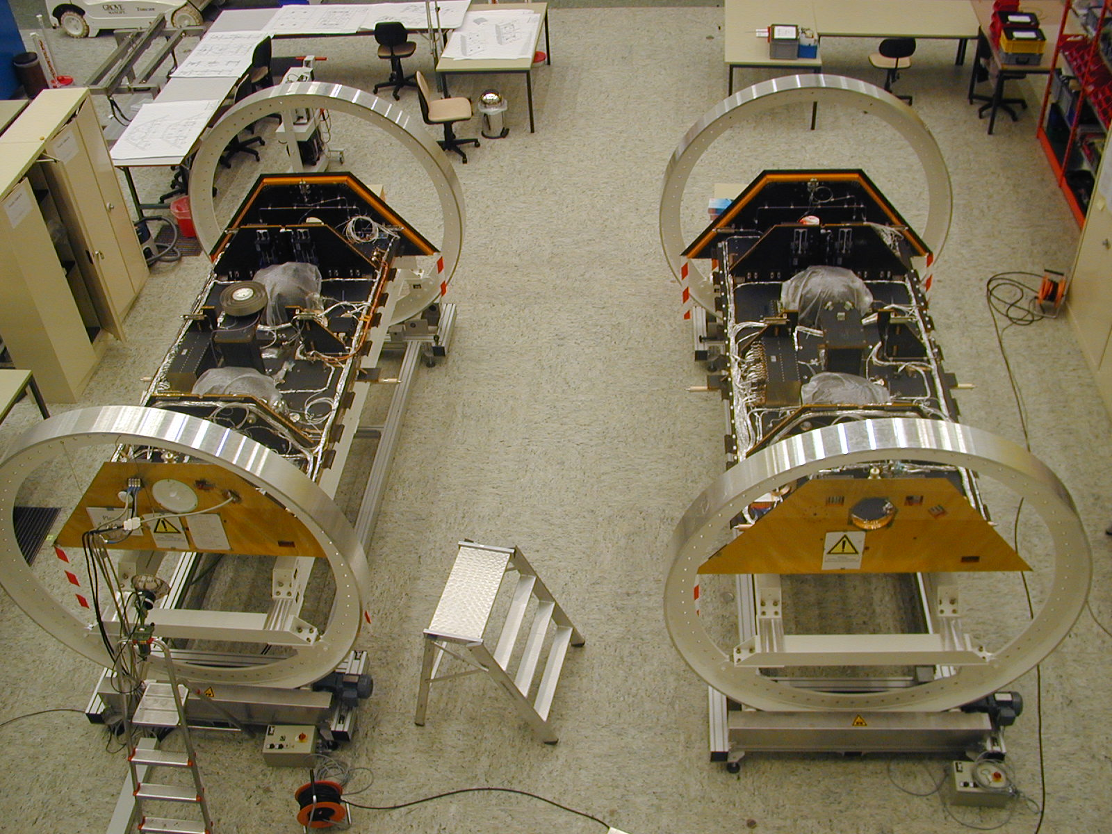 The GRACE satellites are shown without solar panels during component integration in a German clean room.